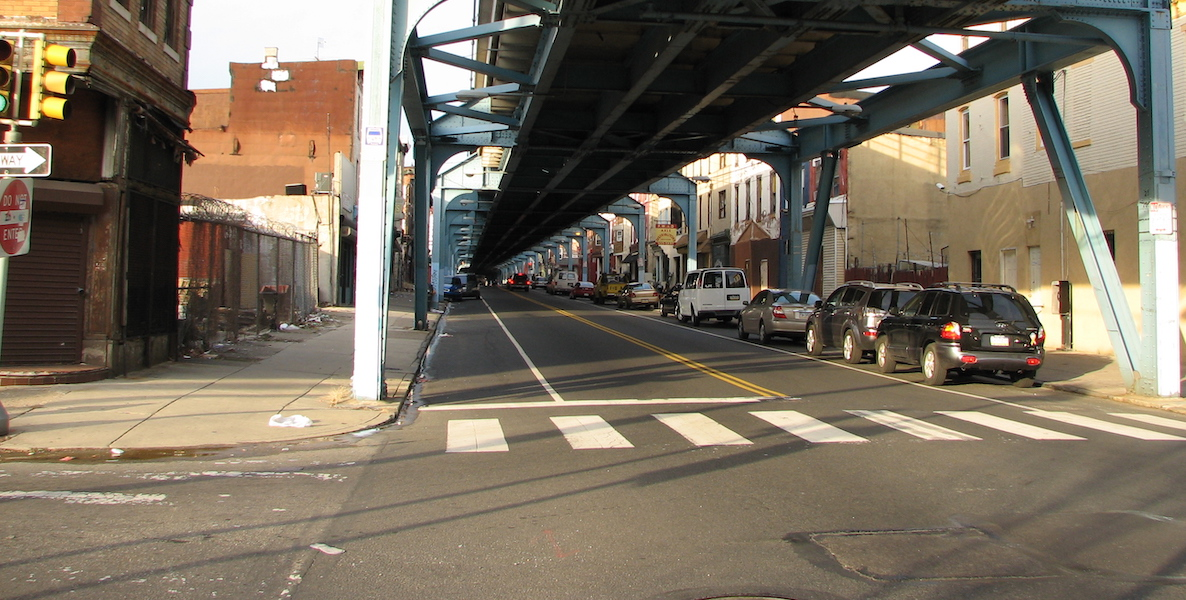 Cars and local businesses line up under the El in Kensington.